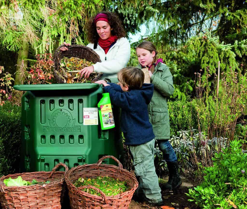 Frau und zwei Kinder befüllen einen Thermokomposter.