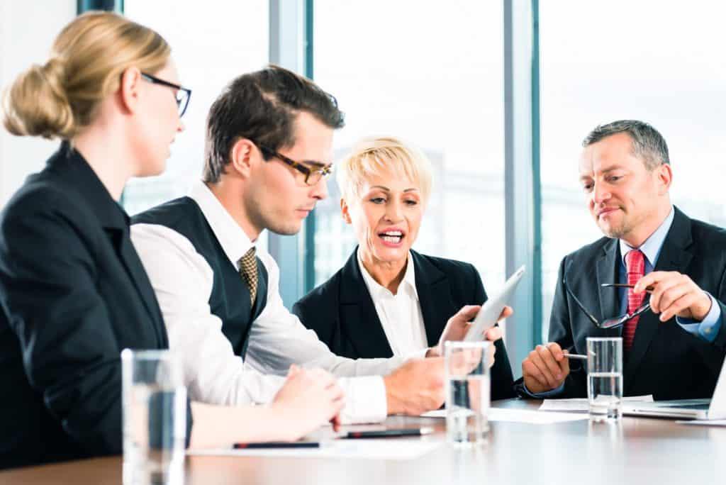 Coaching in der Gruppe: Zwei Männer und zwei Frauen in einem Meeting.