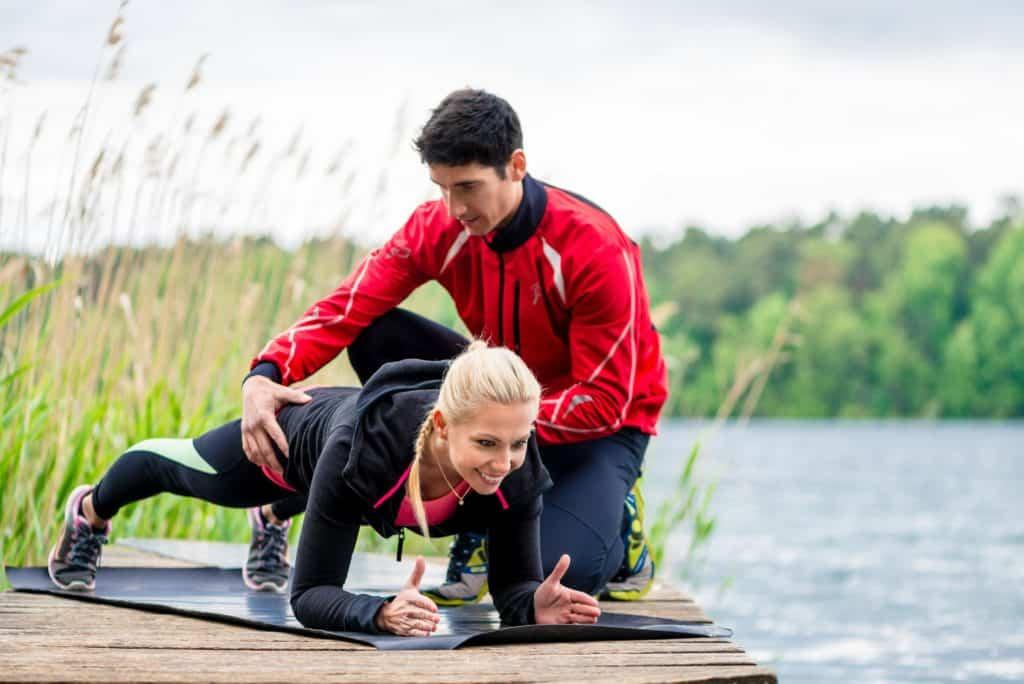 Coaching im Sport: Frau mit persönlichem Fitnesstrainer bei den Liegestützen