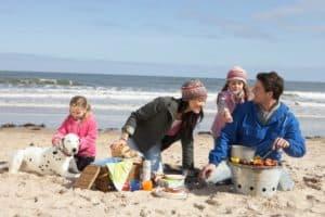 Famiie macht mit ihrem Hund einen Ausflug am Strand.