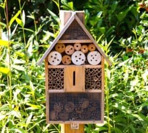 Ein an einen Pfosten angebrachtes Insektenhotel steht im Garten. Es besteht aus verschiedenen Holz- und Bambusstücken, in dessen Löchern sich Nützlinge verstecken können.