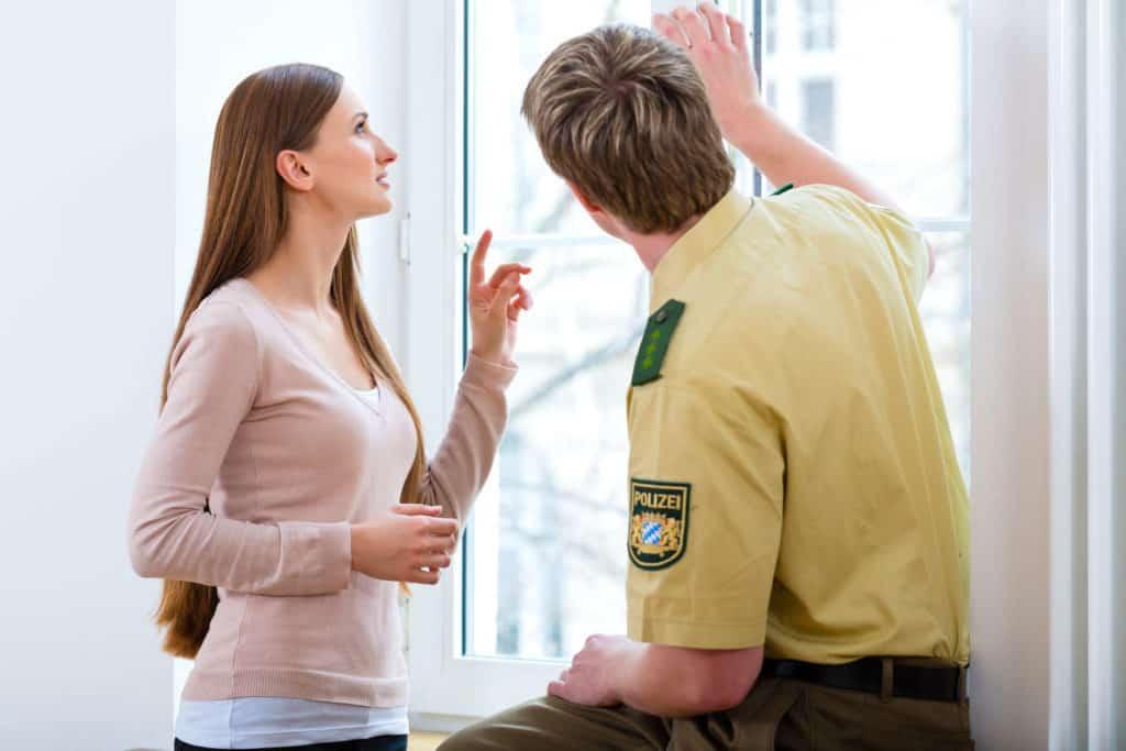 Ein Polizist sitzt auf der Fensterbank und erklärt einer jungen Frau, was in puncto Einbruchschutz zu beachten ist.