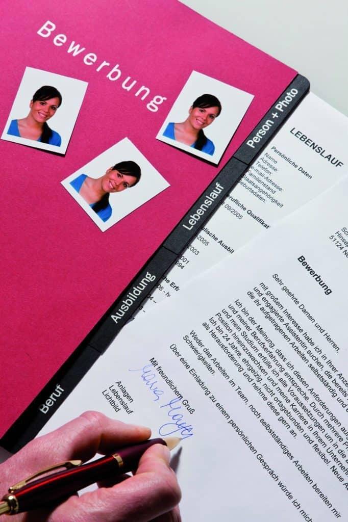 Eine pinkfarbene Bewerbungsmappe mit Anschreiben und Bwerbungsfotos.