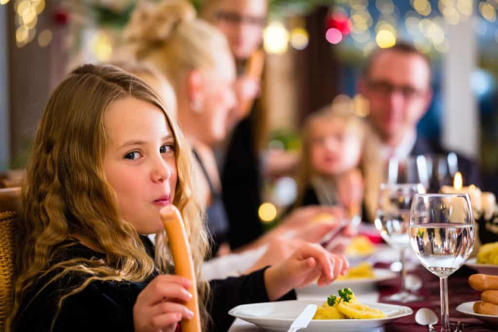 Ein Mädchen sitzt mit seiner Familie an Weihnachten am Esstisch und ist ein Wiener Würstchen. Auf ihrem Teller liegt Kartoffelsalat. Leckeres Weihnachtsessen.