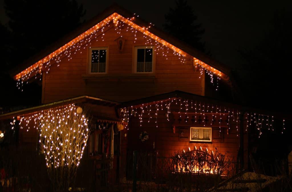 Ein mit Lichterketten geschmücktes Holzhaus sorgt für weihnachtliche Stimmung und hohe Stromkosten.