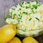 Eine Schale mit Kartoffelsalat, der mit Schnittlauchröllchen bestreut ist.