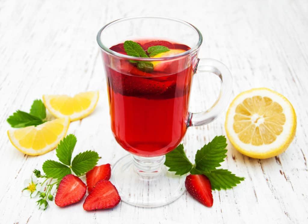Erbeerbowle im Glas mit daneben liegenden Erdbereeren, Zitronen und Zirtonenmelisse dekoriert.