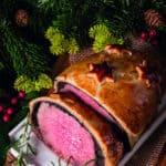 Beef Wellington zu Weihnachten, ein ganzes Rinderfiflet im Blätterteigmantel, aufgeschnitten auf dem weihnachtlich dekorierten Esstisch.