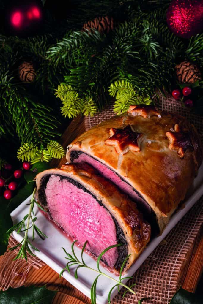 Filet Wellington, ein ganzes Rinderfiflet im Blätterteigmantel, aufgeschnitten auf dem weihnachtlich dekorierten Esstisch.