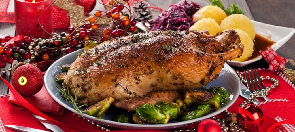 Eine ganze gebratene Ente auf dem weihnachtlich dekorierten Esstisch. Beilagen sind Knödel und Rosenkohl. Leckeres Weihnachtsessen.