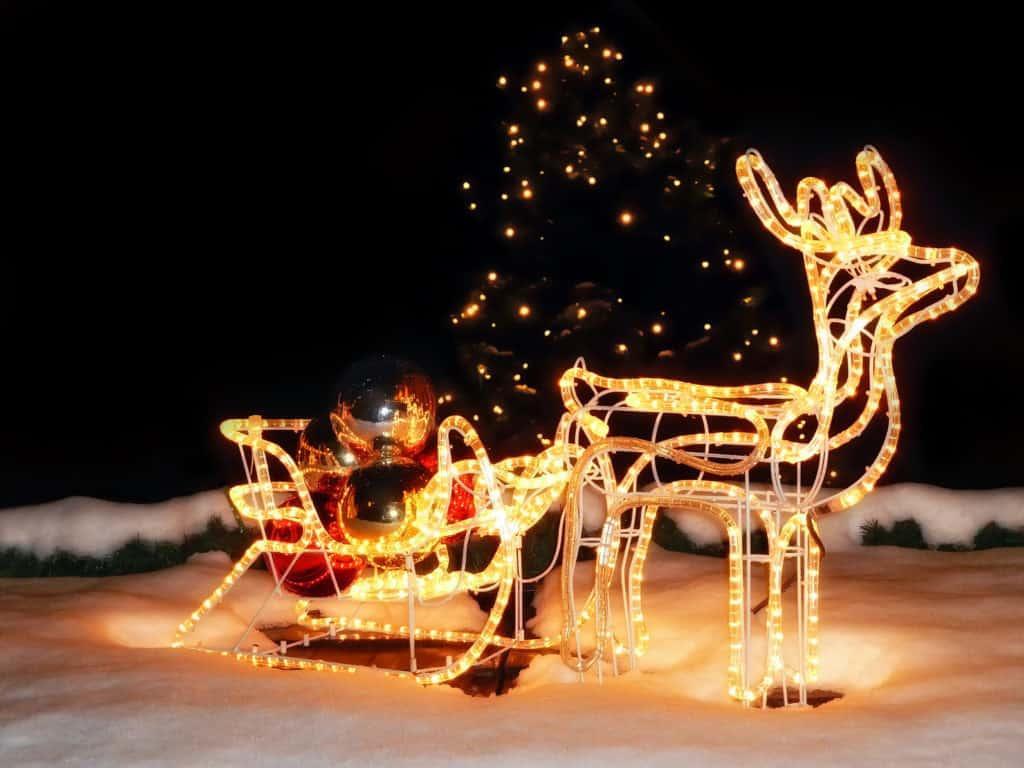 Ein Rentierschlitten aus Lichterschläuchen im Schnee sieht in der Dunkelheit schön aus.