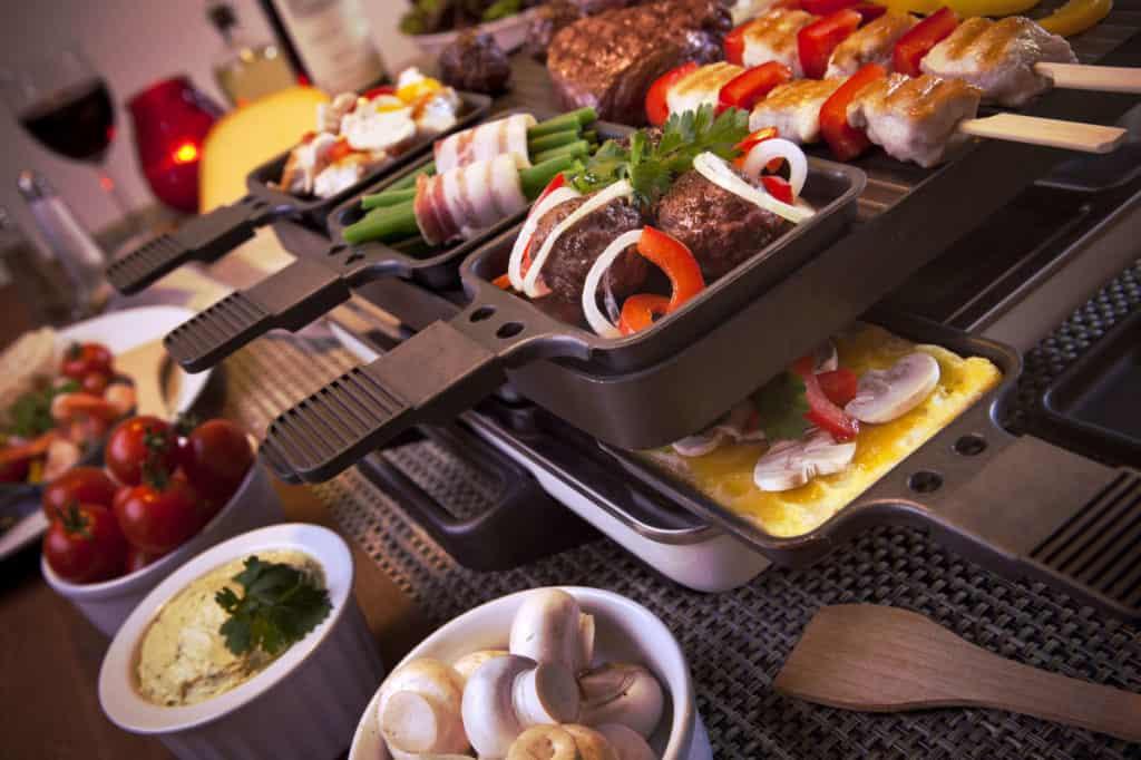 Weihnachtsessen: Raclette-Essen mit Tischgrill. Die Pfännchen sind gefüllt mit verschiedenen Zutaten. Um den Grill herum stehen Schalen mit Pilzen, Tomaten und Quark.