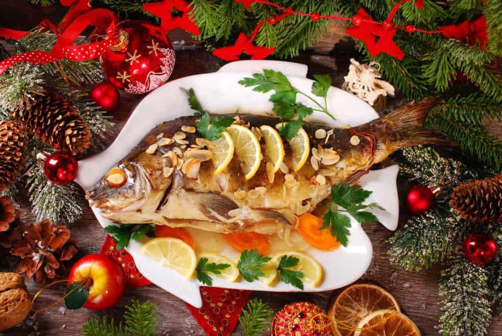 Ein ganzer Weihnachtskarpfen auf dem weihnachtlich dekorierten Esstisch ist ein beeindruckendes Weihnachtsessen.