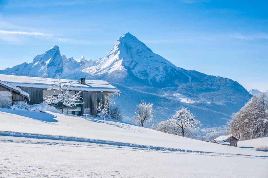 Winterurlaub: Vor einer schneebedeckten Bergkulisse steht ein Ferienhaus, umgeben von mit Raureif bedeckten Bäumen.