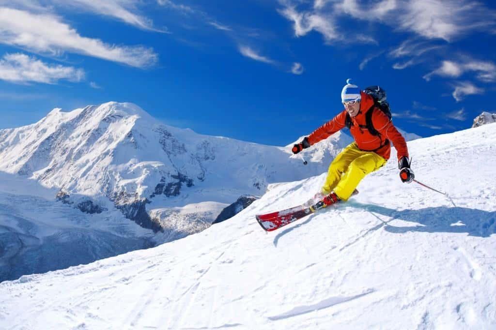 Ein buntgekleidete Skiefahrer fährt kurvenreich einen Schneehang hinab. Der Himmel ist strahlend blau und im Hintergrund sieht man ein verschneites Bergmassiv.