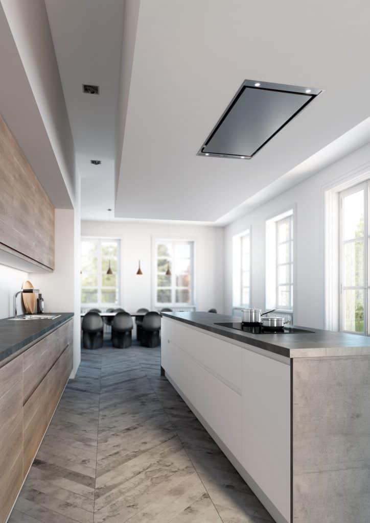 Puristische Wohnküche: im Vordergrund Küchenzeile und gegenüber weißer Küchentresen. Im Hintergrund langer Esstisch mit vielen dunklen Stühlen.