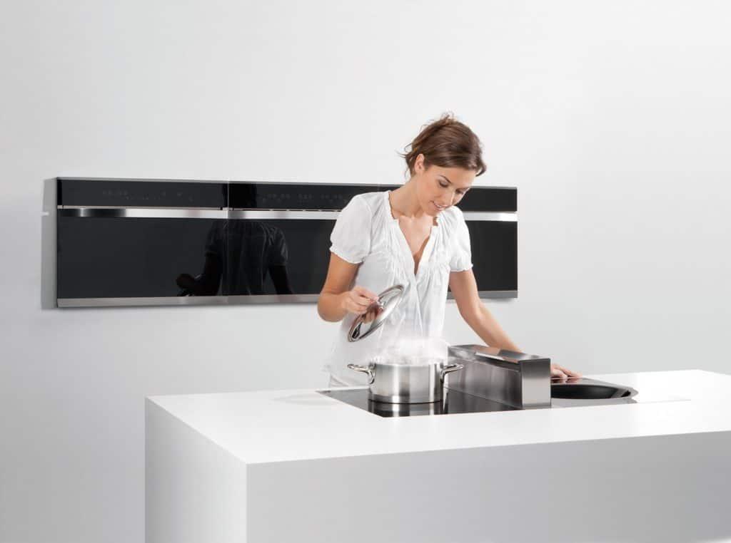 Wohnküche: Frau hebt den Glasdeckel eines Kochtopfes. In dem Kochfeld ist der Dunstabzug integriert.
