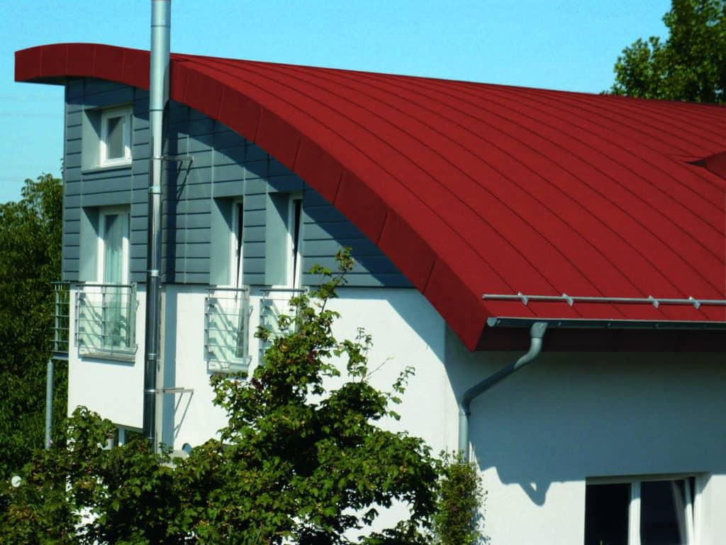 Modernes Haus mit grauer Fassade und rotem Dach aus Zink