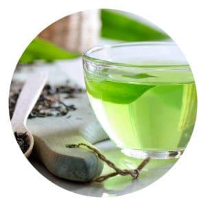 Eine Tasse aus Glas gefüllt mit Grünem Tee. Naben ein Holzbrett mit losem Tee.