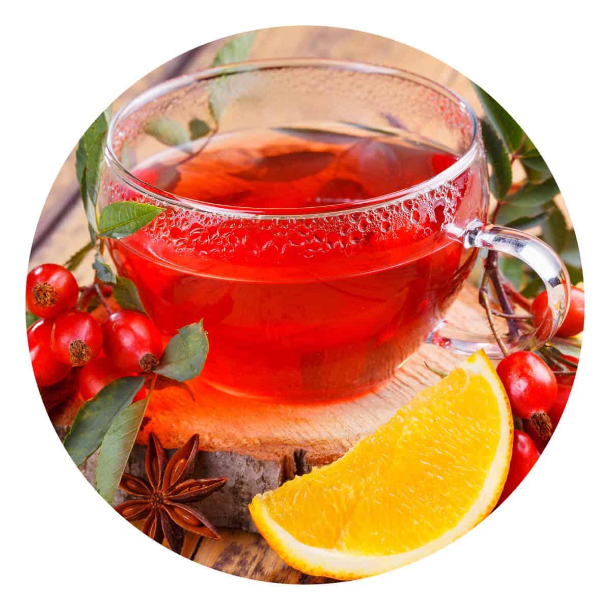 Eine Glastasse mit rotem Früchtetee, links und rechts dekoriert mit roten Früchten, Zimt und einem Stück Zitrone.