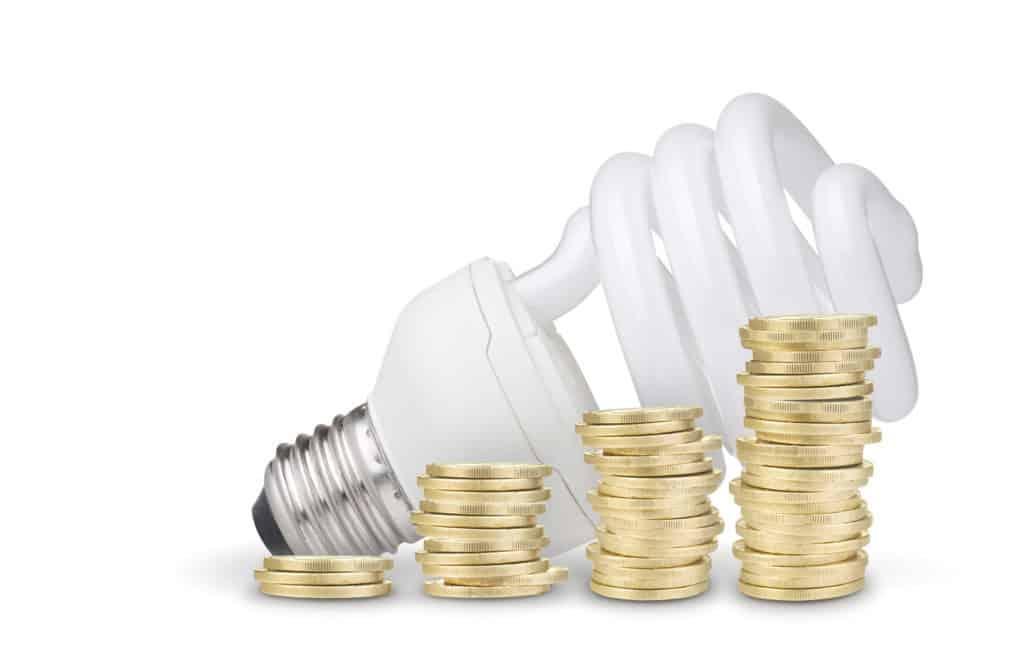 Energiesparlampe und vier Stapel mit Centstücken - Strom sparen mit energieeffizienten Lampen.