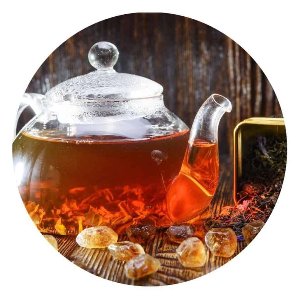 Eine Glaskanne gefüllt mit Schwarzem Tee, daneben eine umgekippte Dose mit Teeblättern, im Vordergrund Kandisstückchen.