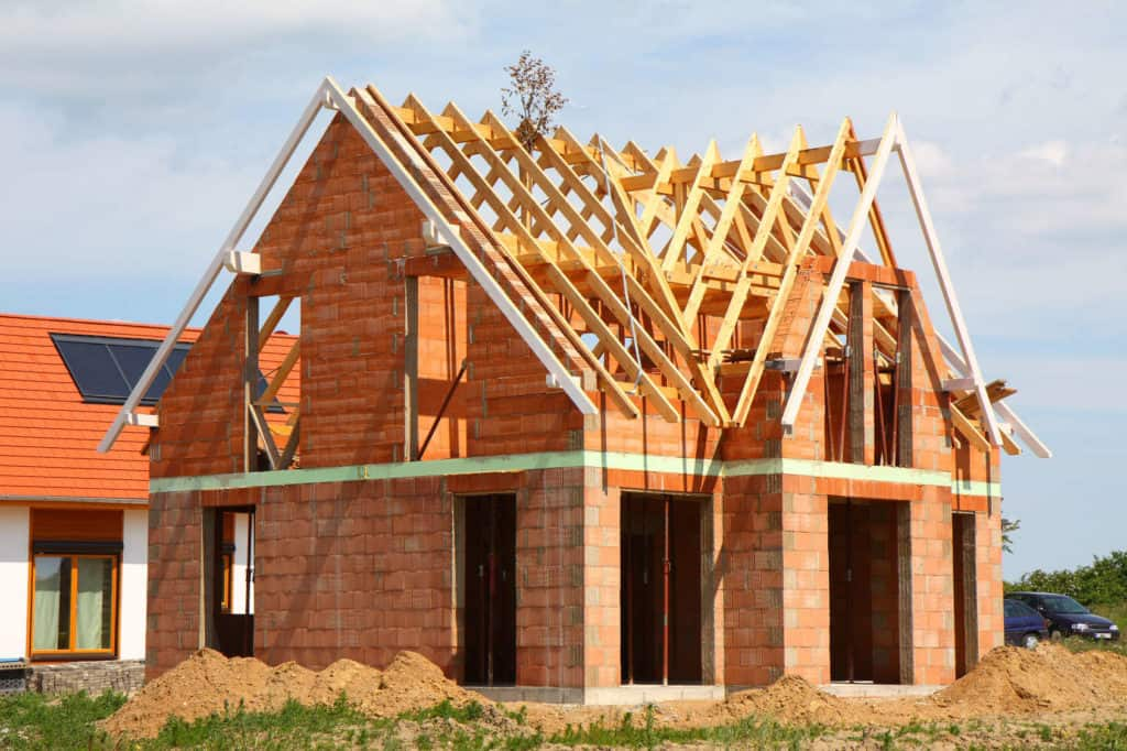 Der Rohbau eines Hauses mit roten Backsteinen und hölzernem Giebel. Wichtig ist energieeffizient zu dämmen.