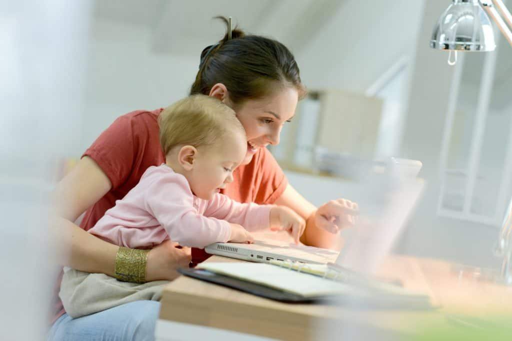 Homeoffice: Frau arbeitet mit Baby auf dem Schoss am Laptop.