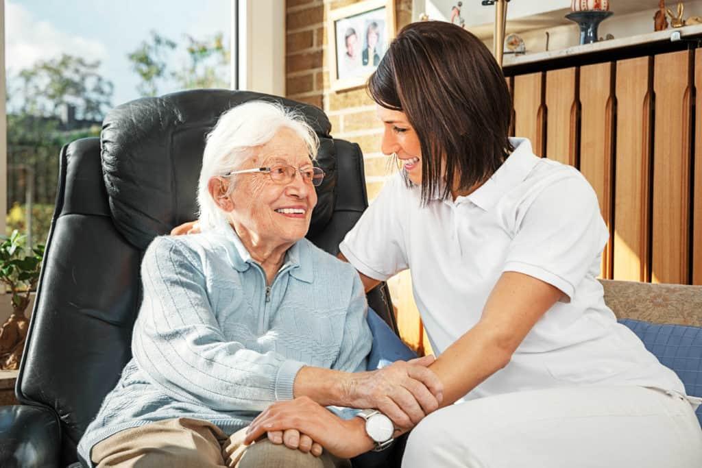 Pfegefachkräfte: Seniorin sitzt im Sessel nehmen einer sympatischen jungen Pflegerin.
