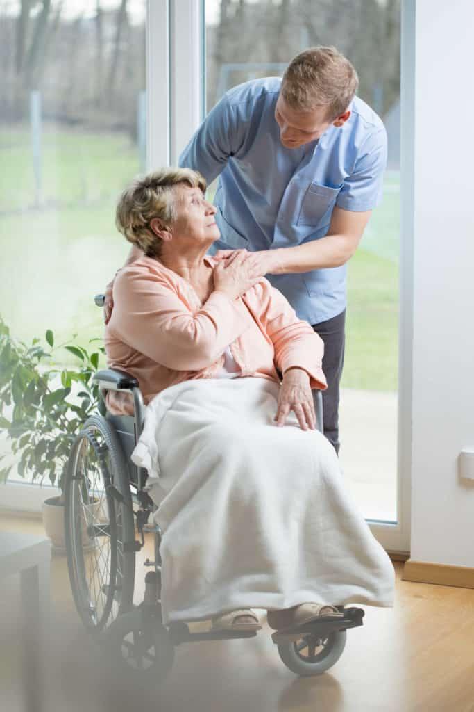 Junger Mann als Pflegefachkraft kümmert sich um ältere Dame im Rollstuhl - Pflegefachkräfte