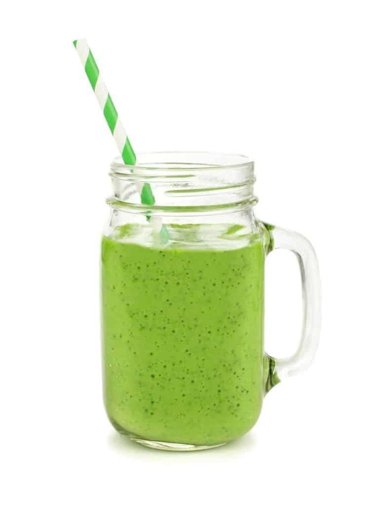 Grüner Smoothie im Glas und mit grün-weiß gestreiftem Strohhalm