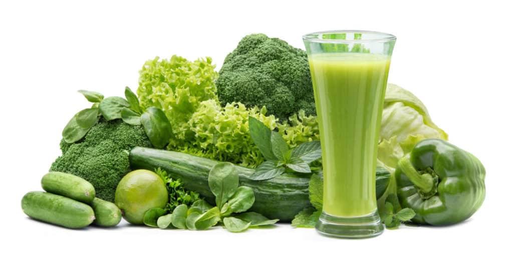 Ein grüner Smoothie im Glas vor seinen Grundzutaten wie Brokkoli, Paprika, Gurke, Salaten und Kräutern