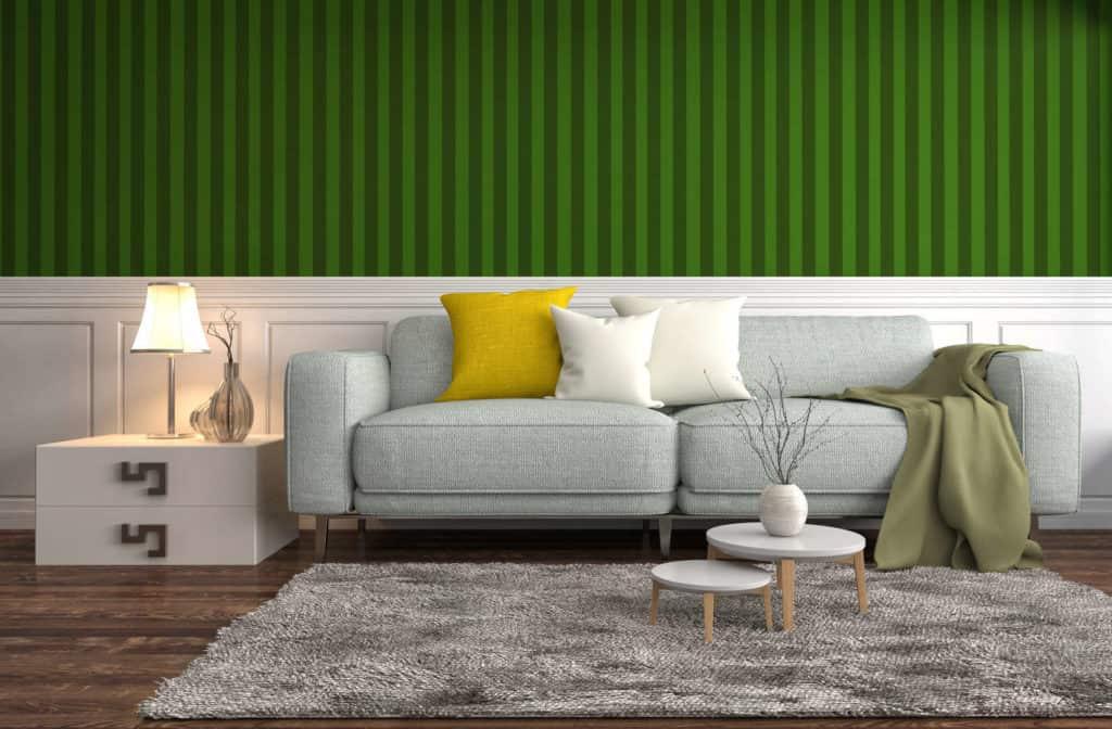 Die Wandgestaltung hinter dem grauen Sofa mit weißer Holztäfelung und grün gestreifter Mustertapete bringt Frische in die eigenen vier Wände.
