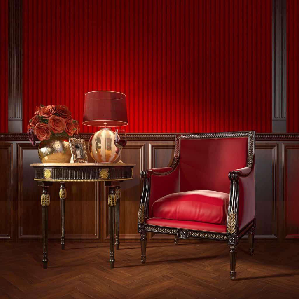 Rot bezogener Ledersessel und Tisch mit Goldverzierungen passen perfekt zu einer Wandgestaltung aus naturbelassenem und rot gestrichenem Holz.