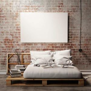 Eine Wandgestaltung aus freiliegendem Mauerwerk passt perfekt zu den aktuellen Palettenmöbeln wie diesem Bett.