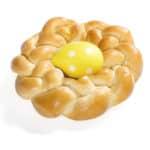 Kleiner geflochtener Kranz aus Dinkelteig mit einem gelben Osterei in der Mitte – guten Appetit zu Oster.