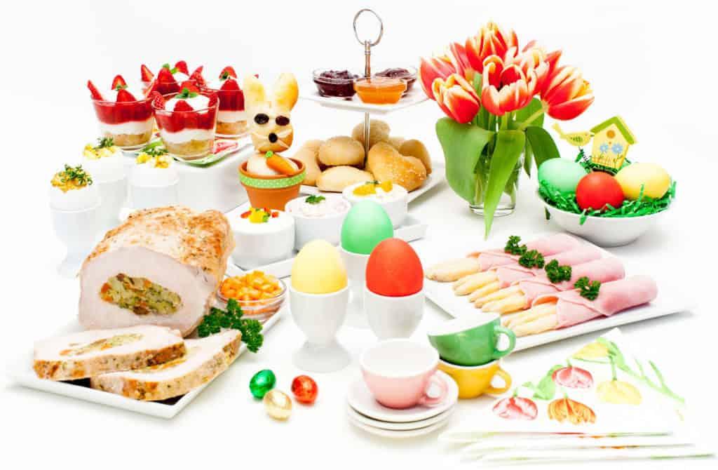 Leckereien für das Frühstüch zu Ostern: bunte Eier im Eierbecher, Spargel in Schinken, gefüllter Braten, Brötchen und Marmelade, Quark mir Erdbeeren und Tulpen, Osterhase und kleine Schokoeier als Deko.