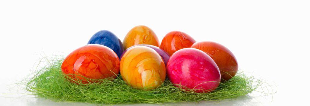 Bunt gefärbte Ostereier in grünem Grasnest vor hellem Hintergrund – Ostern