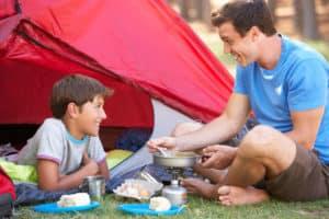 Vater und Sohn im Campingurlaub sitzen vorm Zelt und kochen mit einem Gaskocher.
