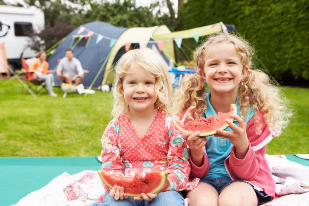 Zwei Mädchen im Campingurlaub essen Melone. Im Hintergrund ihre Eltern und das Zelt.