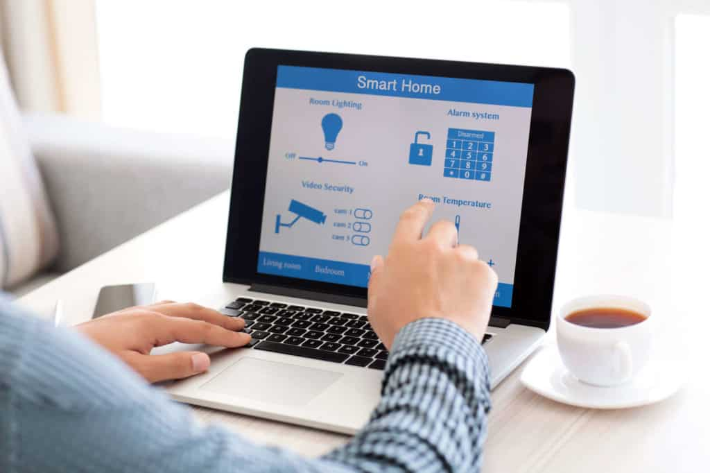 Mann sitzt mit Kaffeetasse am Laptop und steuert Licht, Alarmanlage, Raumtemperatur und Videoüberwachung per Smart Home.