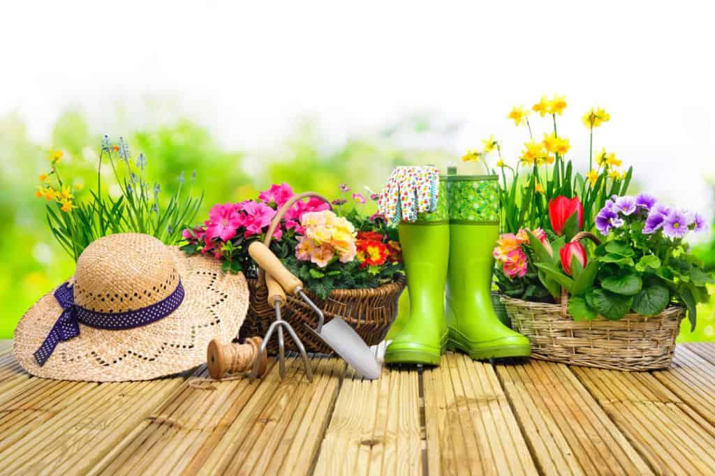 Sommerhut, grüne Gummistiefel, Gartenwerkzeug und bunte Blumen in Körben: Alles für ein neues Bluemenbeet