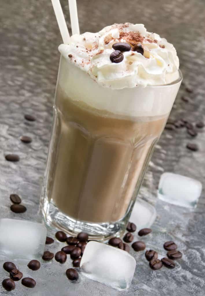 Tolle Kaffee Rezepte: Eiskaffee im Glas und daneben Kaffeebohnen und Eiswürfel.