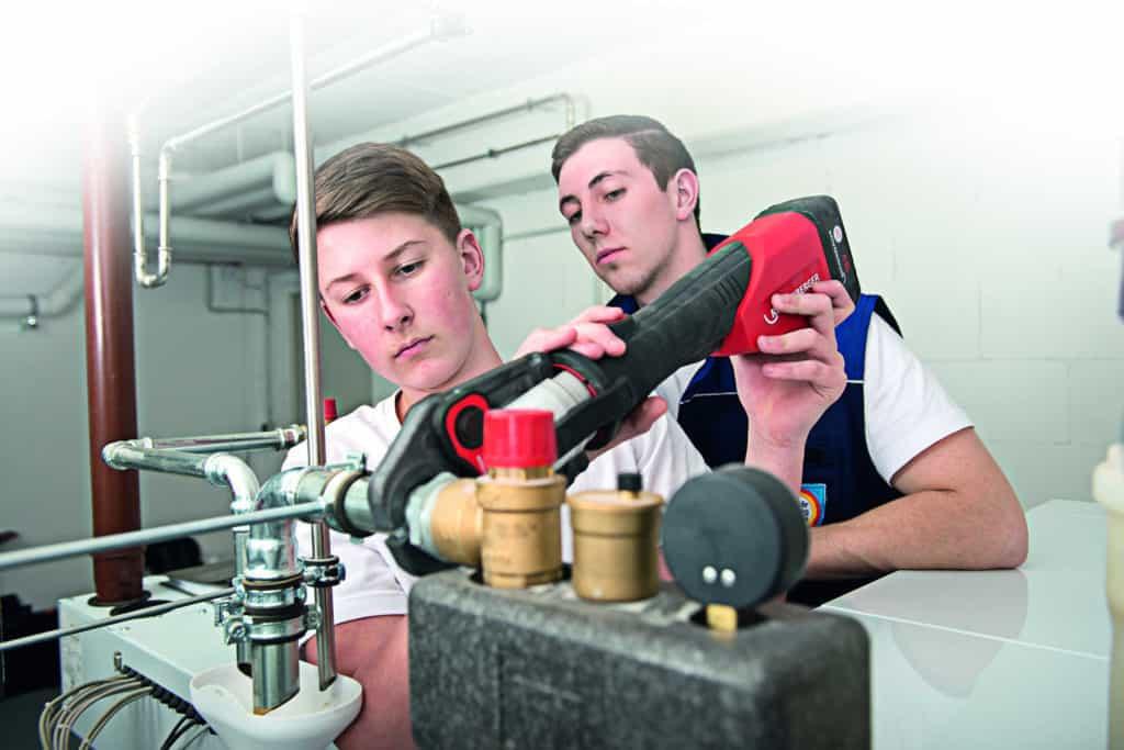 Schülerpraktikum: Ein Junge arbeitet unter Aufsicht ein einer Heizung.