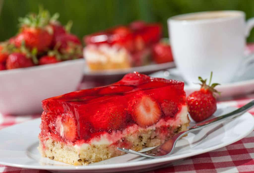 Ein Stück Erdbeertorte, im Hintergrund eine Schüssel mit frischen Erdbeeren und eine weiße Tasse – die Erdbeersaison hat begonnen.