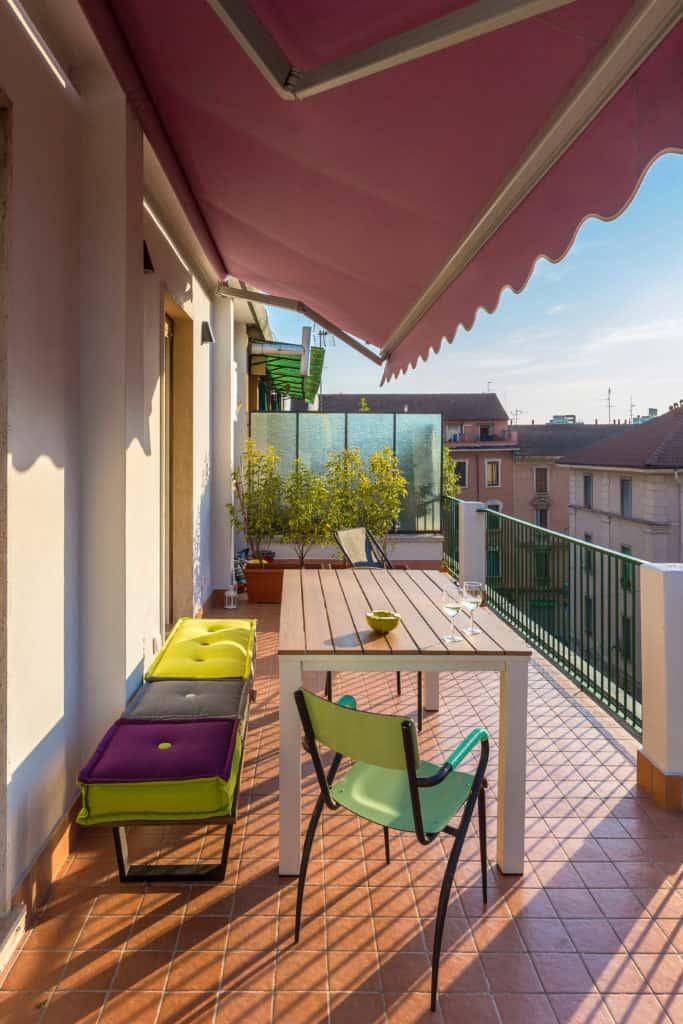 Halbausgefahrene rote Markise über einem Balkon, auf dem ein Tisch und mehrere Sitzgelegenheiten stehen.