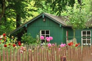 Grünes Gartenhaus in einem Garten mit Zaun und bunten Blumen.