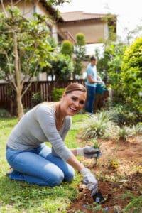 Ein Paar pflanzt im Garten an und gießt die Blumen.