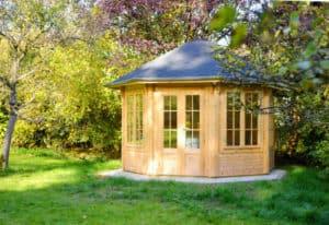 Ein hölzernes secheckiges Gartenhaus mit großen Fenstern steht im Garten.