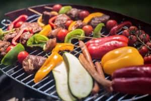 Gemüse, Würstchen und Grillspieße liegen auf einem Grillrost.